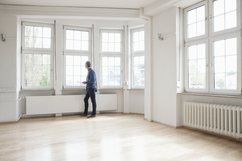Man looking out of window in empty apartment - RBF004689