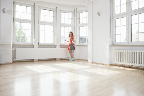Woman looking around in empty apartment - RBF004707