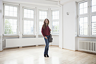 Woman looking around in empty apartment - RBF004713