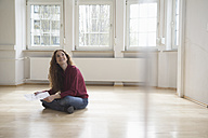 Woman sitting on floor in empty apartment looking around - RBF004719