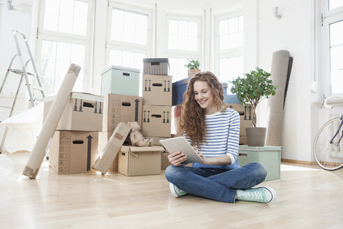 Woman surrounded by cardboard boxes using digital tablet - RBF004722