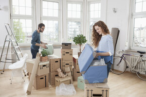 Couple in new apartment unpacking cardboard boxes - RBF004728