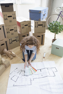 Woman surrounded by cardboard boxes with color samples and construction plan on floor - RBF004737