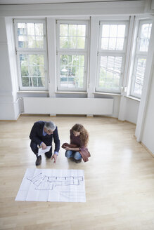 Real estate agent showing construction plan to client in empty apartment - RBF004743