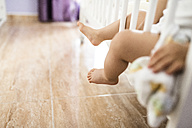 Naked legs of baby boy sitting in his cot - JASF000984