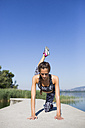 Young woman doing exercise on pier, lifting leg - MRAF000078