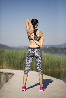 Young woman doing exercise at lake - MRAF000081