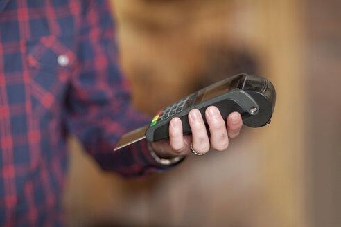 Man holding credit card reader - ZEF008929