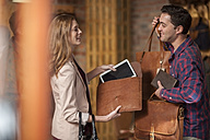 Shop assistant showing leather bags to woman - ZEF008935