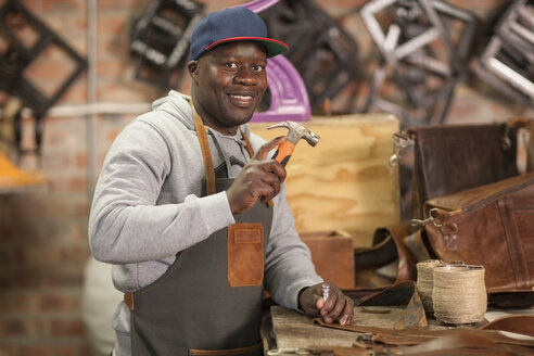 Portrait of smiling man working with hammer in leather workshop - ZEF008965