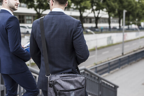 Two young businessmen walking together in the city - UUF007972