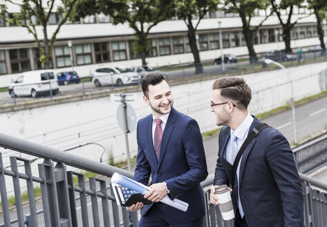 Two young businessmen walking together in the city - UUF007975