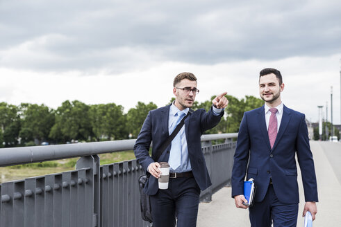 Two young businessmen walking together in the city - UUF007978