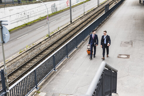 Businessmen on business trip walking with wheeled luggage - UUF007981