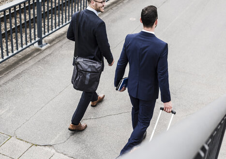 Businessmen on business trip walking with wheeled luggage - UUF007987