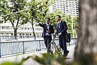 Businessmen walking with bicycle in the city, talking - UUF007999