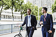 Businessmen walking with bicycle in the city, talking - UUF008002