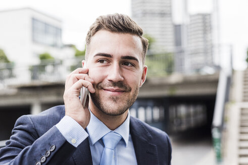 Portrait of a young businessman talking on the phone - UUF008008
