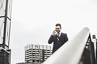 Young businessman standing at railing, using smart phone - UUF008011