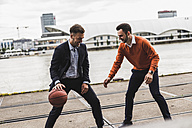 Two colleagues playing basketball after work - UUF008032