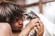 Little boy holding tabby kitten pulling funny face - VABF000666