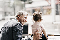 Businessman with little daughter working on laptop in cafe - KNSF000010