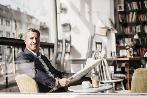 Businessman sitting in a cafe reading newspaper - KNSF000013