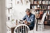 Mature man sitting in cafe reading at digital tablet - KNSF000040