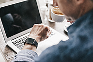 Mature man drinking coffee while working at laptop, looking at smartwatch - KNSF000046