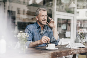 Mature man sitting in cafe talking on the phone - KNSF000052