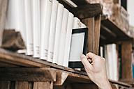 Hand taking e-book from book shelf - KNSF000055