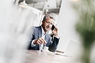 Businessman sitting in cafe, working - KNSF000064