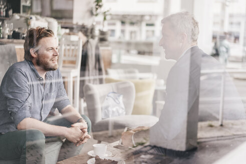 Businessman consulting customer in cafe - KNSF000082