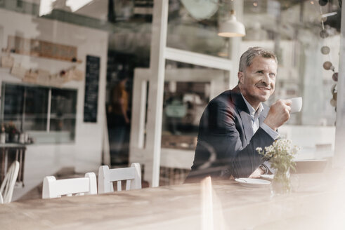 Businessman in cafe drinking coffee - KNSF000088