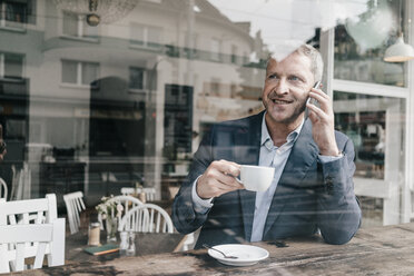Businessman in cafe using smart phone - KNSF000091