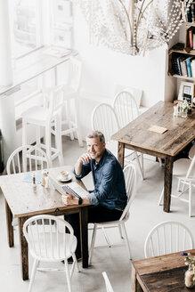 Mature man sitting in cafe using laptop - KNSF000103