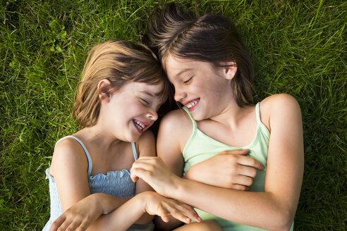 Two sisters lying in meadow having fun - LVF005111