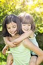 Girl giving her little sister a piggyback ride in the garden - LVF005114