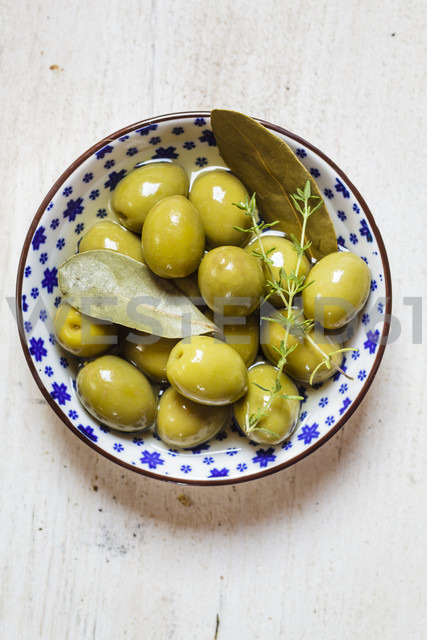 green olives in bowl with thyme and bay leaf - SBDF003034 - Susan Brooks-Dammann/Westend61