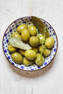 green olives in bowl with thyme and bay leaf - SBDF003034