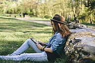 Woman sitting on a meadow using digital tablet - AKNF000048