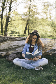 Woman sitting on a meadow reading a book - AKNF000057