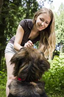 Portrait of smiling woman giving her mongrel a treat - MIDF000753