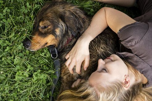 Young woman relaxing with her dog on a meadow - MIDF000759