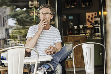 Smoking man sitting in front of a coffee shop - FMKF002752