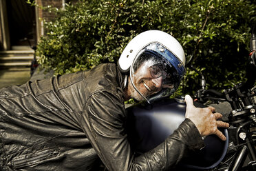 Smiling man wearing motorcycle helmet and leather jacket lying on his motorbike - FMKF002773