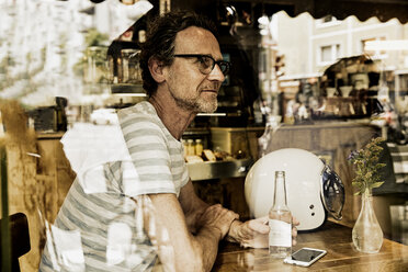 Man sitting behind windowpane of a coffee shop - FMKF002776