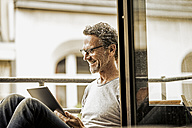 Smiling man sitting on balcony using digital tablet - FMKF002779