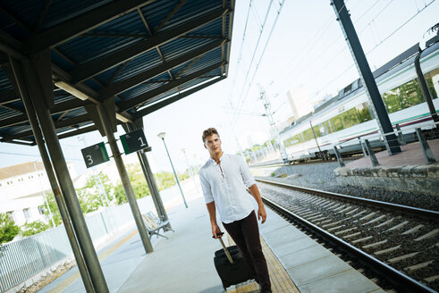 Young man with suitcase walking at station platform - KIJF000532