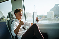Young man taking a selfie with a tablet on a train - KIJF000544